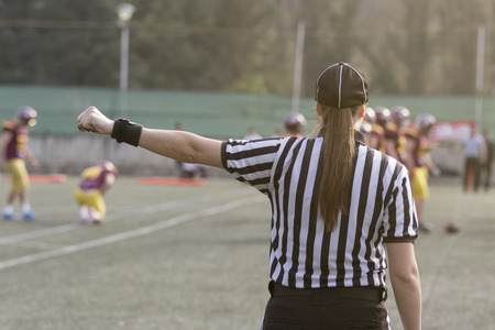 Female football judge in stripped black and white shirts on the field. Players in the background. Foto de archivo