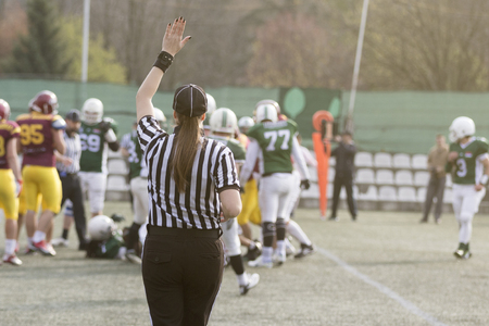 Female football judge in stripped black and white shirts on the field. Players in the background. Banco de Imagens