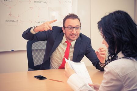 Businessman is angry to his female coworker and threatens with forefinger as he is not satisfied with her work. Business stress and conflict concept. Office life.