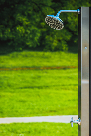 Outdoor shower details and green grass in the background. Suitable for designers to add people showering.   Stock Photo