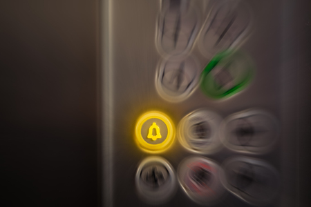 Close up of elevator alarm and panic button on control panel. Button is switched on. Emergency and call for help concepts.