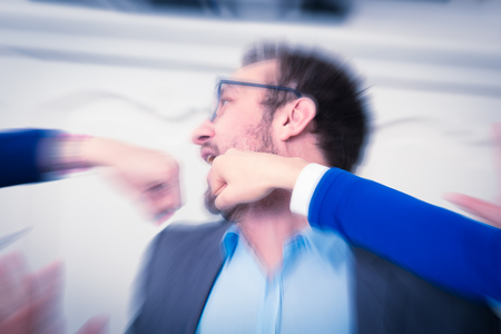 Businessman hit in the face by two female fists. Punching, smashing and business disagreement concepts.