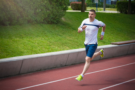Morning training. Jogger running on the red running track. Workout, sport, healthy lifestyle concepts. Stock Photo