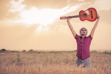 Young happy retro styled man raising acoustic guitar up in the air and standing in wheat field. Sunrise and clouds in the background. Music, art and lifestyle concepts.