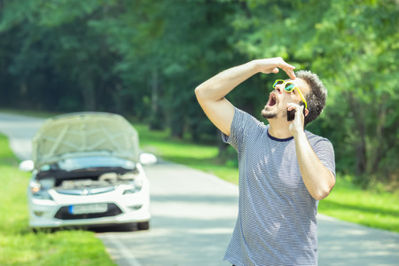 Young modern stressed man making call with road assistance service by using smartphone. Car with raised hood at the roadside in the background.  Stock Photo
