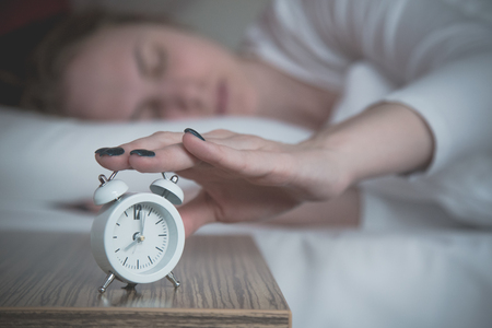Close up of woman turning off the alarm clock. Morning, time for work and waking up concepts.