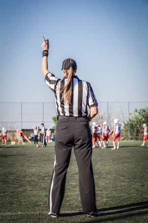 Female Football referee observing the match