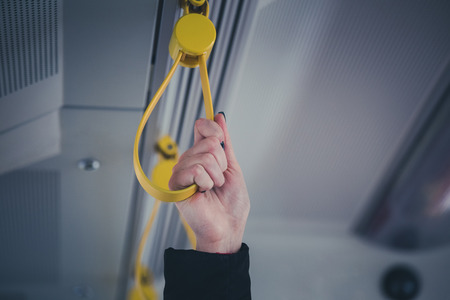 Close up of hand holding handle in bus, tram, metro or subway. Public transportation concept Stock Photo