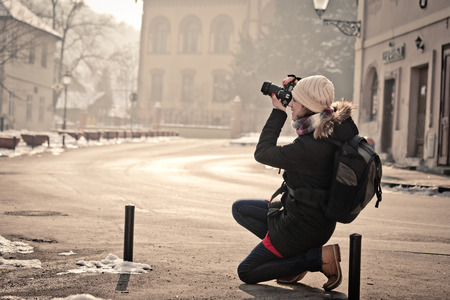 Portrait of female street photographer shooting urban scene with DSLR camera Stock Photo