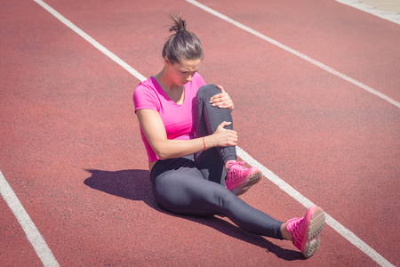 Female sitting on running track and holding her injured leg. Accident during jogging Reklamní fotografie - 97031451
