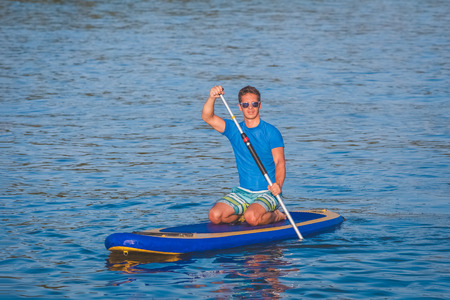 Portrait of young guy surfing on paddle board Stock Photo
