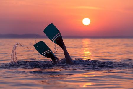 Close up of scuba diver feet with snorkel fins start diving at sunset Stock fotó