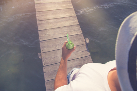 Tourist walking on wooden pier and holding fresh kiwi juice. Tourism and healthy lifestyle concepts