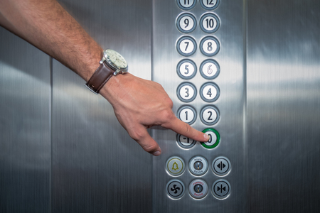 Male forefinger pressing the zero floor button in the elevator. Iron made interior.