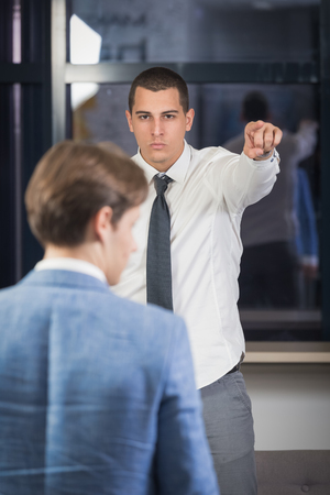 Executive firing worker by pointing out with his forefinger to go out of the office.