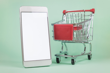 Shopping cart miniature and blank screen smartphone on green background. Online shopping e-commerce concept