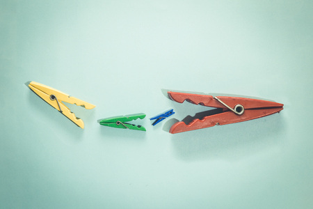 Clothespins devour each other. Food chain minimal concept.