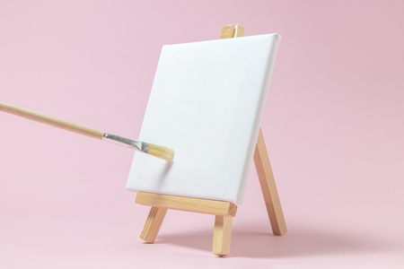 blank art canvas on easel and paintbrush against pastel pink stock