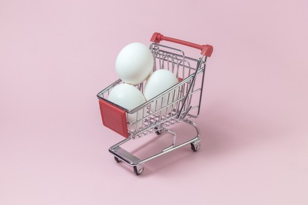 Shopping trolley model full of white eggs against pastel pink rose background minimal concept. Space for copy. Stock Photo