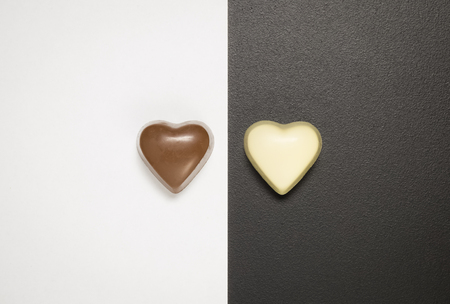 Flat lay of heart shape pralines on black and white background. Minimal sweet and love concepts.