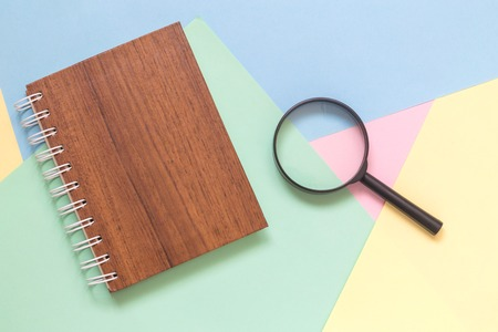 Magnifying glass and notebook against colorful pastel background flat lay minimal creative concept.