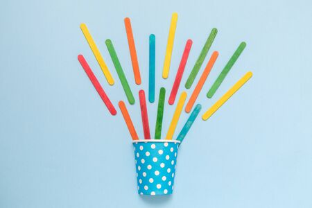 Flat lay of paper cup polka design and colorful ice cream sticks on pastel blue background minimal creative concept. Stock Photo
