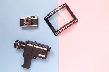 Retro vintage analog film camcorder, photo camera and picture frame on pastel background minimal technology creative concept.