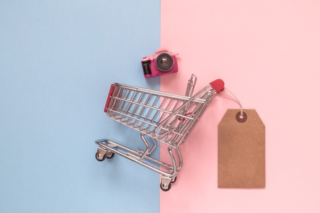 Flat lay of dslr toy model camera and small shopping cart with price tag on pastel background minimal creative concept. Reklamní fotografie