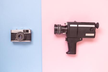 Retro vintage analog film camcorder and photo camera on pastel background minimal technology creative concept. Reklamní fotografie