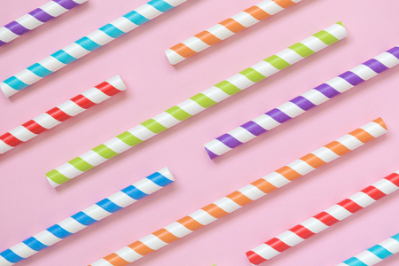 Colorful striped drinking straws pattern on pastel pink background minimal creative concept