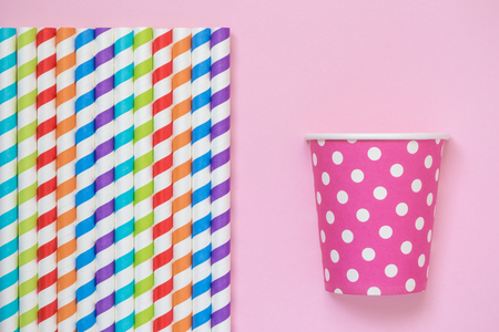 Colorful striped drinking straws and paper cup polka design on pastel pink background minimal creative concept. Space for copy.