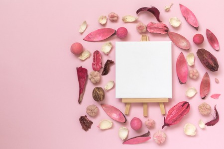 Dried flowers, leaves and plant parts with easel for artists and blank canvas on pastel rose background minimal creative art flat lay concept. Reklamní fotografie