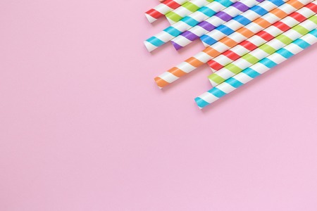 Colorful striped drinking straws on pastel pink background minimal creative concept. Space for copy. Reklamní fotografie