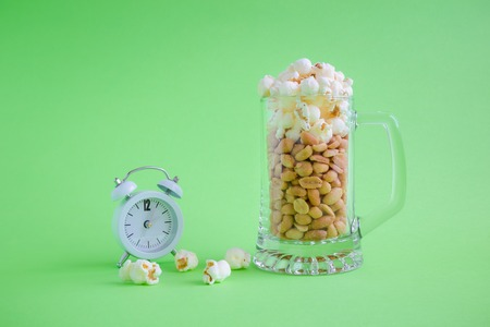 Peanuts with popcorn in form of beer and foam in mug and alarm clock on green background minimal creative concept. Space for copy. Reklamní fotografie