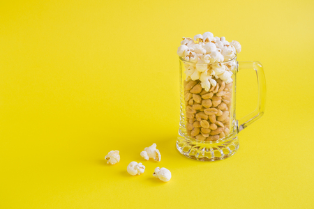 Peanuts and popcorn in form of beer and foam in mug on yellow background minimal creative concept. Space for copy. Reklamní fotografie