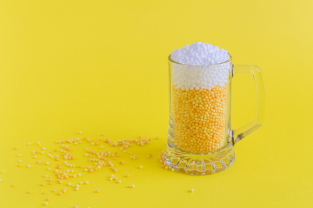 Beer mug abstract made of foam balls on yellow background minimal creative concept. Space for copy.