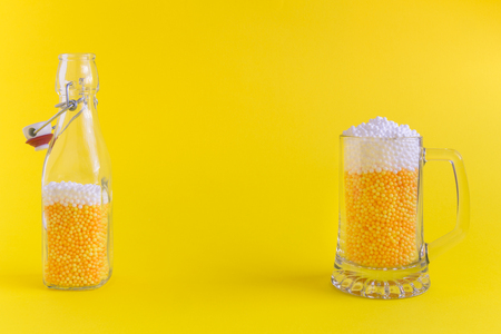Beer mug and bottle abstract made of foam balls on yellow background minimal creative concept. Space for copy.