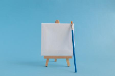 Blank art canvas on easel and paintbrush against pastel blue background. Artist minimal concept. Space for copy. Reklamní fotografie