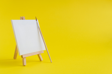 blank art canvas on easel and paintbrush against yellow background
