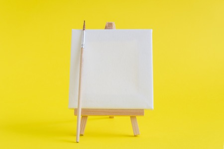 Blank art canvas on easel and paintbrush against yellow background. Artist minimal concept. Space for copy. Reklamní fotografie