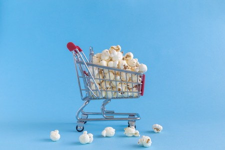 Shopping trolley toy full of popcorn on pastel blue background minimal concept. Stock Photo