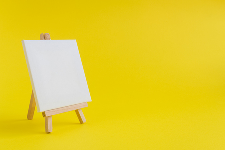 Easel for artists and blank canvas miniature on pastel yellow background. Art minimal concept. Reklamní fotografie