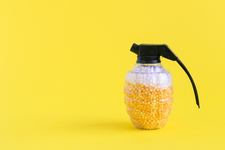 Hand grenade toy bomb full of foam balls in form of beer and foam minimal creative concept. Space for copy.
