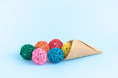 Ice cream made of colorful rattan balls and cone on pastel blue background minimal creative concept. Space for copy.