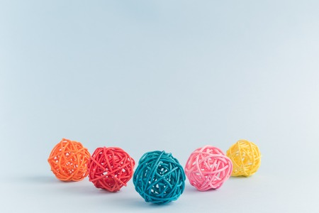 Colorful rattan balls on pastel blue background minimal creative concept. Space for copy.