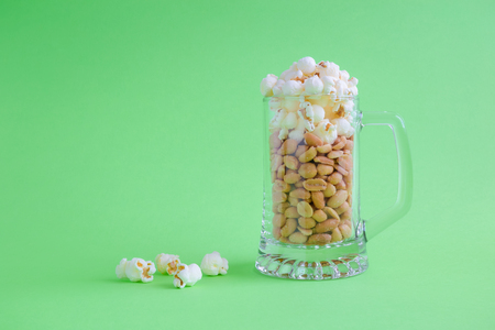 Peanuts and popcorn in form of beer and foam in mug on green background minimal creative concept. Space for copy. Reklamní fotografie