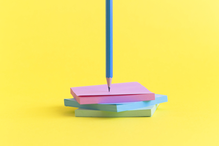 Sticky notes in different colors with pencil on yellow background minimal concept.