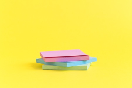 Sticky notes in different colors on yellow background minimal concept. Space for copy.