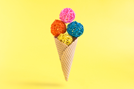 Ice cream made of colorful rattan balls and cone on pastel yellow background minimal creative concept. Space for copy.