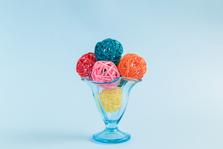 Sundae ice cream with colorful ice cream balls made of rattan balls in cup against pastel blue background minimal concept.